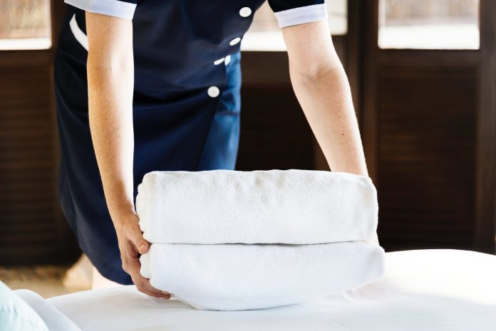 person folding white bed linen