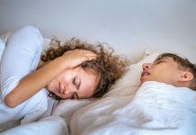 wife closing her ears annoyed by husband's snoring
