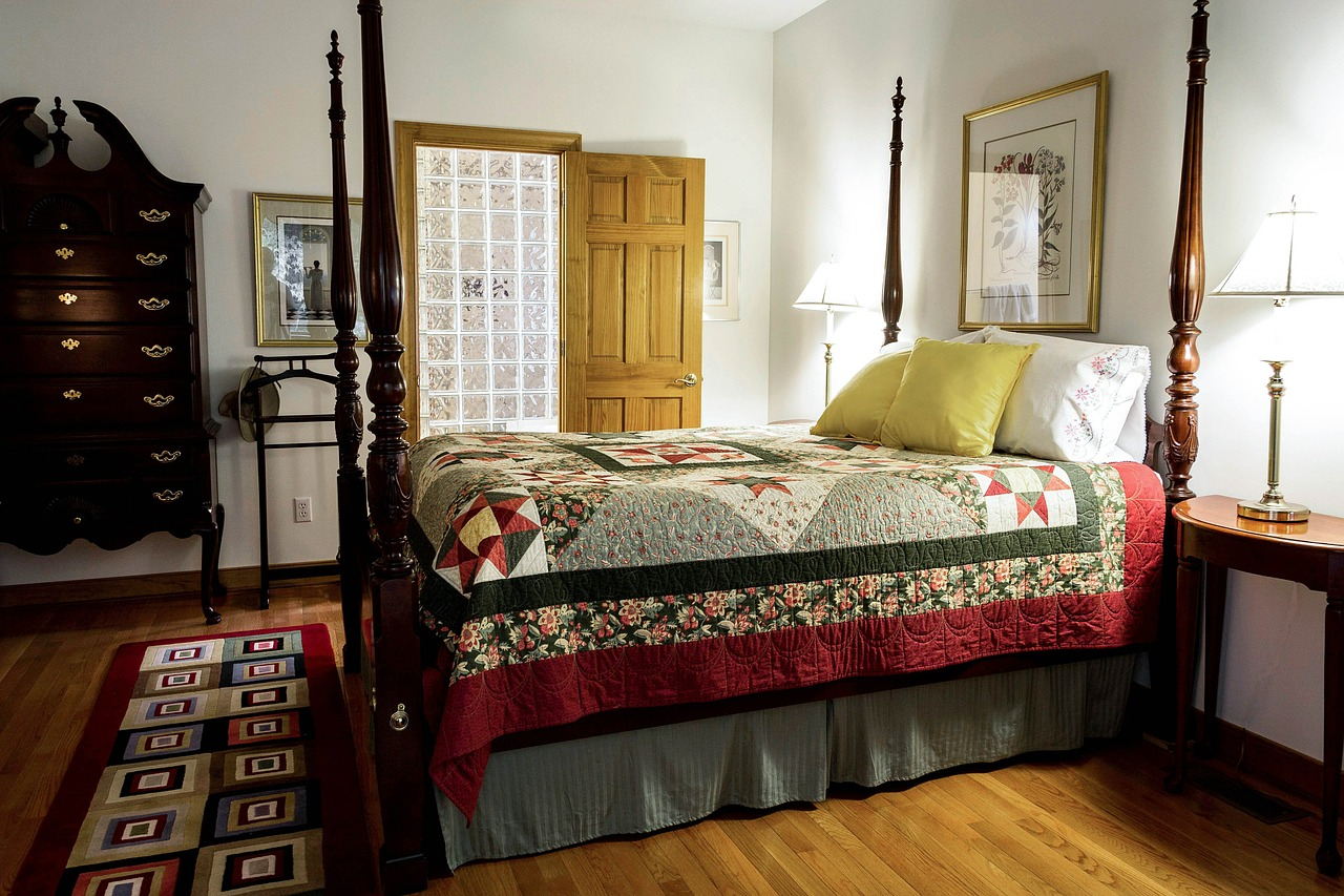 queen size bed with a colorful quit sheet cover